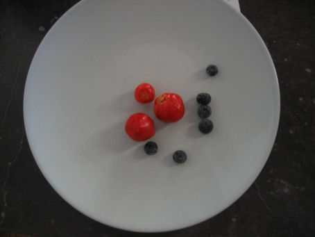 Tiny tomatoes with blueberries for size comparison