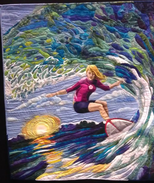 Hang Ten, by Yvonne Chapman. Quilt of a woman surfing a wave at sunset