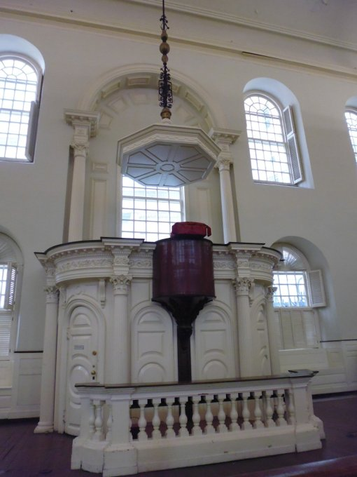 The octagonal thing above the pulpit is a 'sounding board' that helped project the speaker's voice to the up to 5000 people inside the meeting house