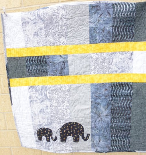 Wide vertical strips of various grey fabrics, split by two yellow horizontal strips, with appliqued elephants