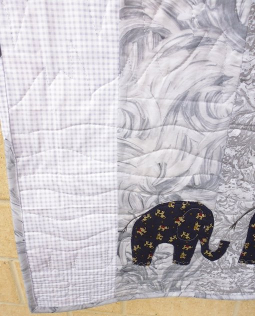 For the quilting, I did narrow wavy lines with grasses popping up every so often to represent the ground below the elephants, followed by wider wavy lines representing heat haze, then spiky lines representing mountains in the distance