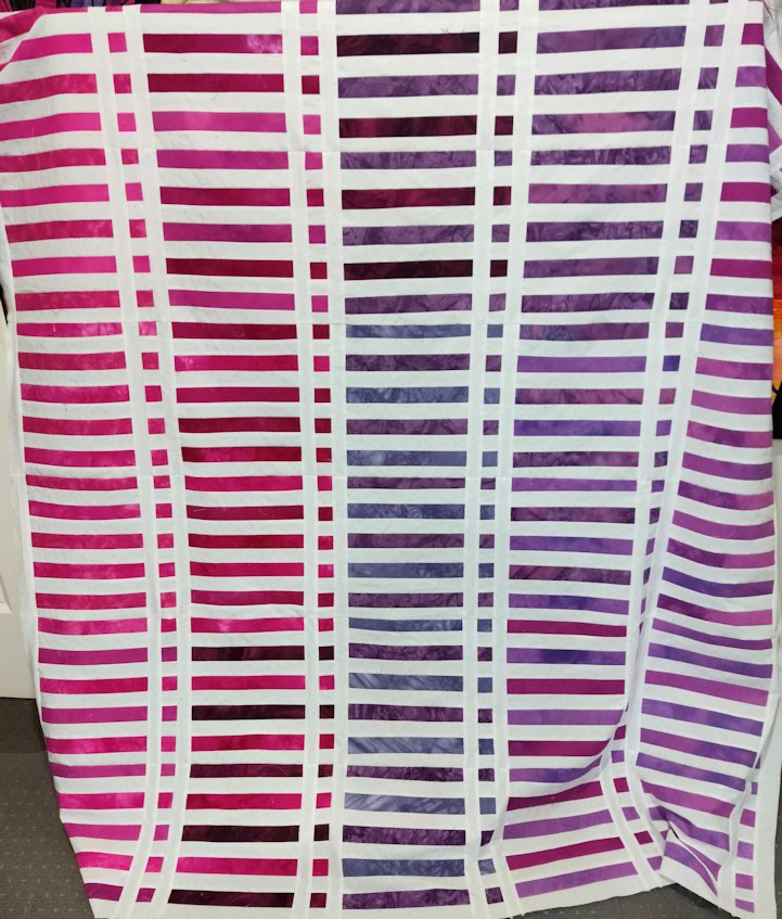 Quilt top in layered rows of graduated pink, purple and white fabrics