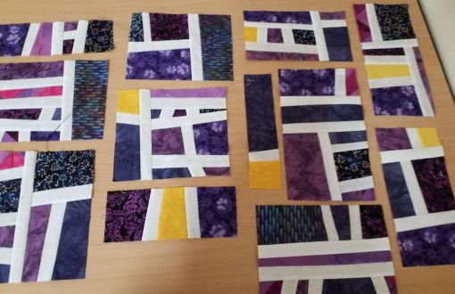 first quilt blocks partially completed -- purples and deep blues with splashes of yellow fabric