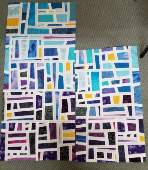 quilt top partially completed -- all aquas and purples with splashes of yellow fabric