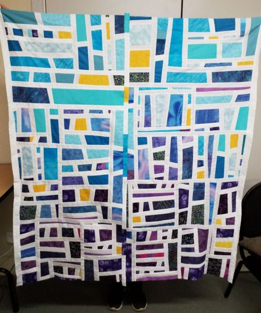 quilt top completed -- all aquas and purples with splashes of yellow fabric